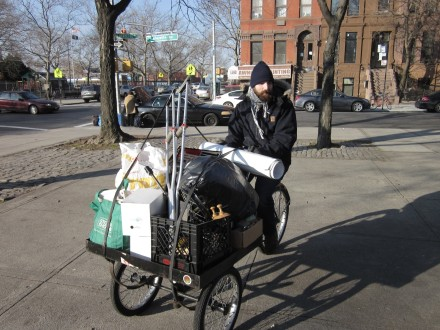 Thaddeus Umpster dropping off supplies on a cargo bike. Photo by Eric Kingrea