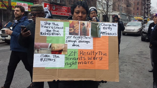Marcia Louisy holds a sign demonstrating her landlord's neglect