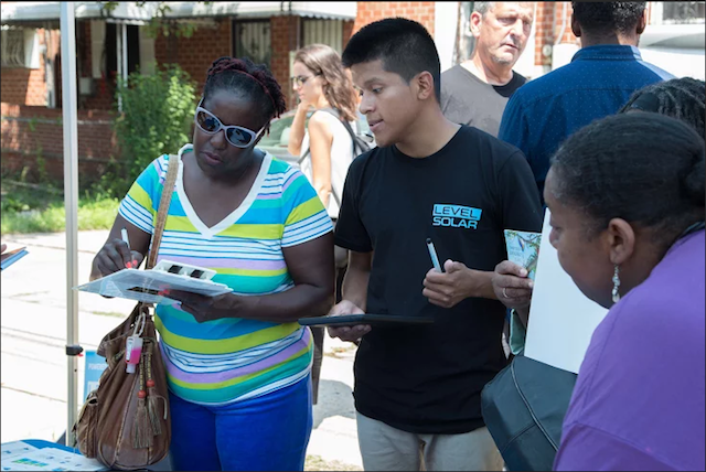 A representative from Level Solar helps a Brownsville resident sign up for a free solar panel installation. Photo via Malcolm Bliss/Level Solar