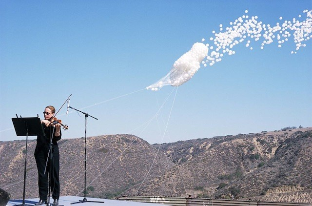 A live score accompanies Jaar's cloud of balloons over the Mexican border. via Highlike.org