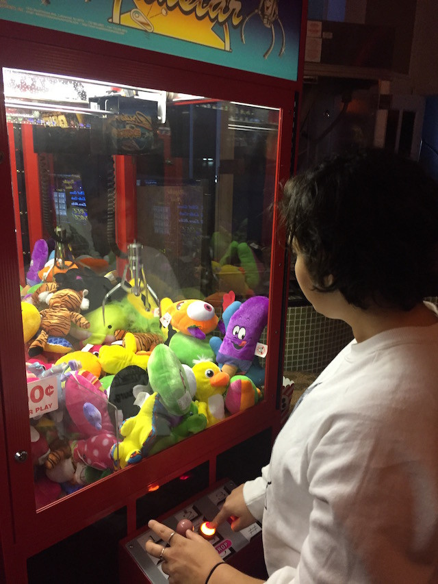 Local youth Sam Corbin tries her hand at the claw machine. It's unclear if the arcade games will survive into the new iteration.